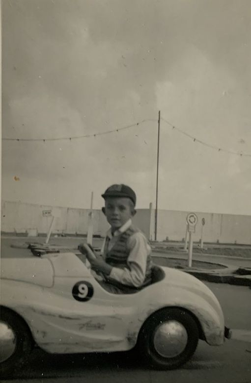 Bobby in a model car on a track.