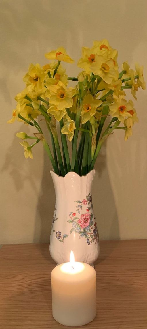 A candle lit for Diddley in front of a vase of Golden Sun Narcissi.