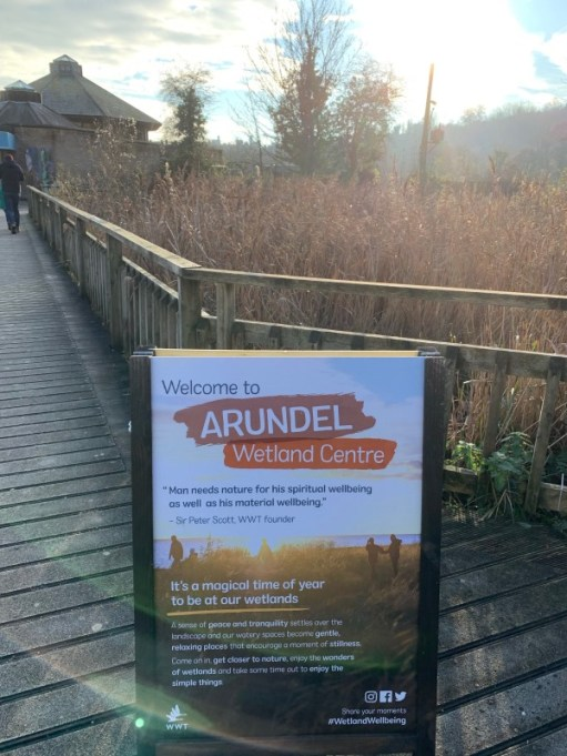 """Sign """"Welcome to the Arundel Wetland Centre"""", with some of the Wetlands in the background."""