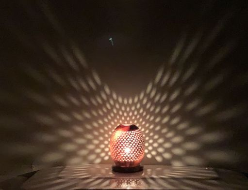 A candle lit for Diddley in a glass jar with diamond patterns which are cast up around the wall behind.