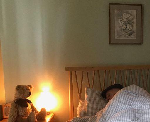 Bertie looking at Bobby asleep in bed.
