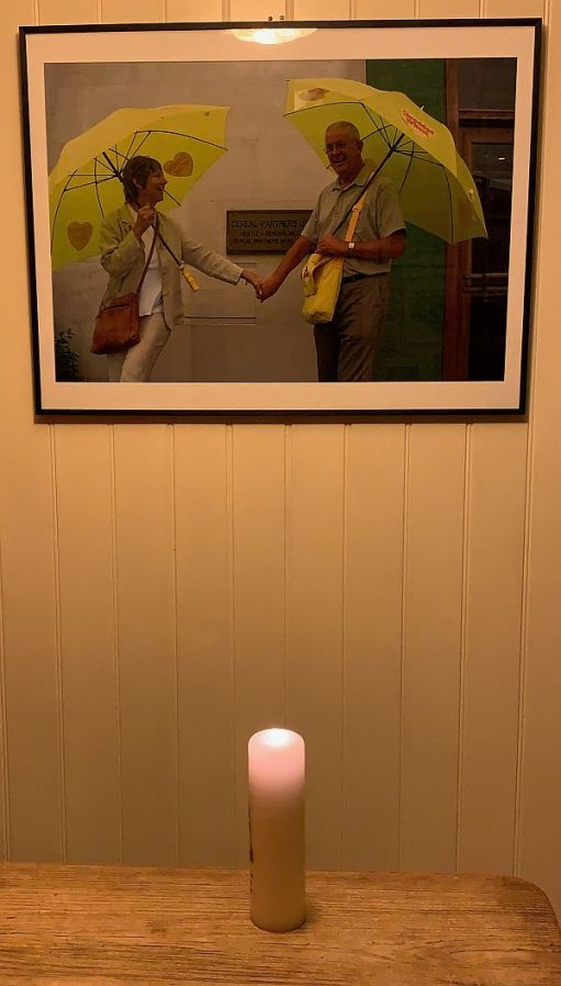 """A candle lit for Diddley in front of the """"Shredded Wheat"""" photograph on the wall."""