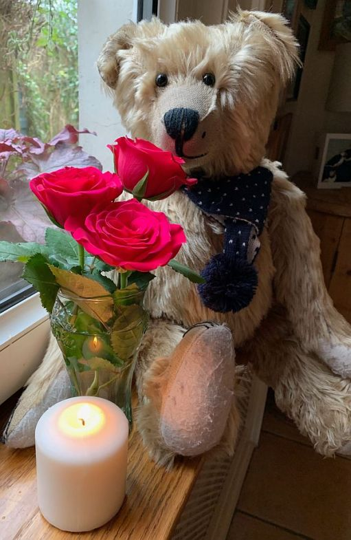 Bertie with the vase of Red Roses in front of him and a candle lit for Diddley in front of them.