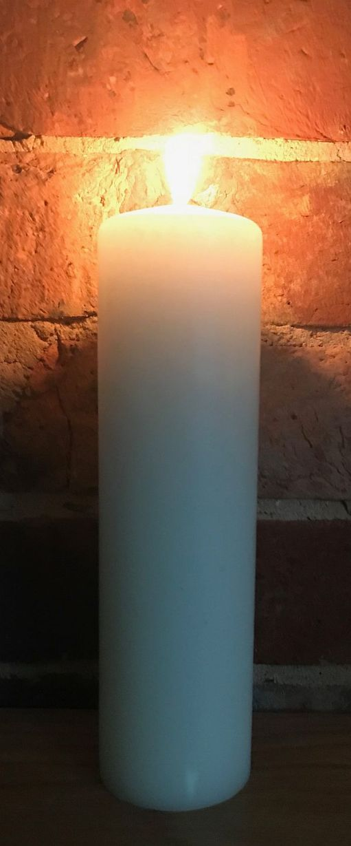 A tall, white candle lit for Diddley (and Gerry Marsden) against a plain brick wall.