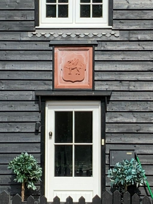 Wooden house in Abinger Hammer with the Wotton Estate Griffin plaque.