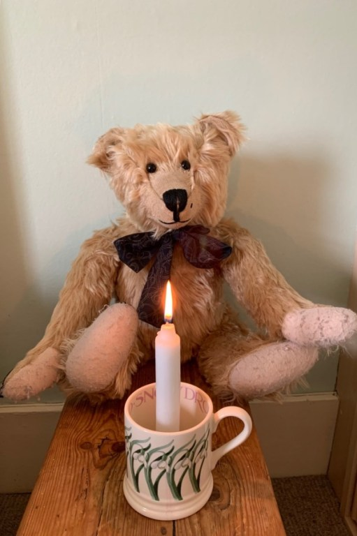 Bertie sat behind a candle lit for Diddley in a mug.