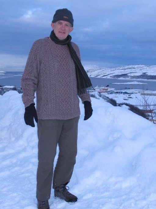 Bobby wearing the fawn Aran jumper on a snow capped mountain in Norway.
