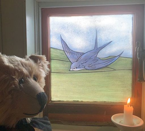 A candle lit for Diddley in front of Diddley's Bluebird window. Bertie is looking on.
