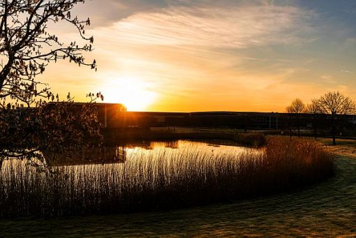 View of the Rolls-Royce plant across the lake looking into the rich colours of the sunset.