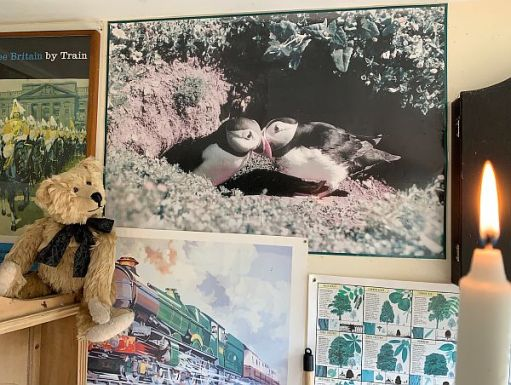 """Bertie in front of Bobby's """"Kissing Puffins"""" picture along with a candle lit for Diddley."""