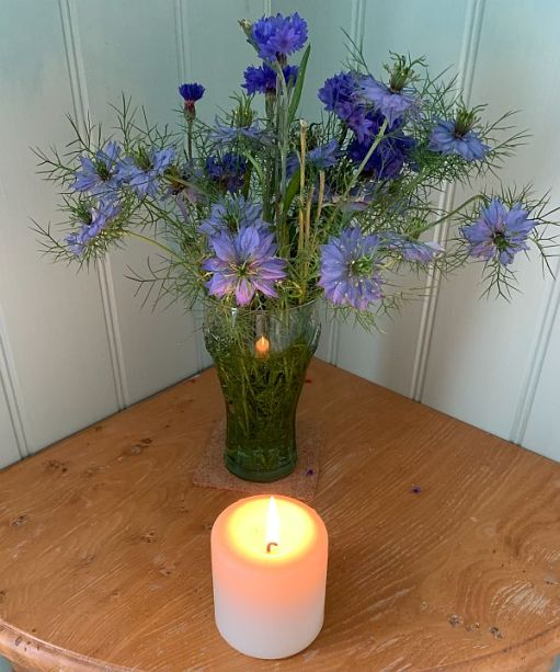 A candle lit for Diddley in front of a vase of Cornflowers.