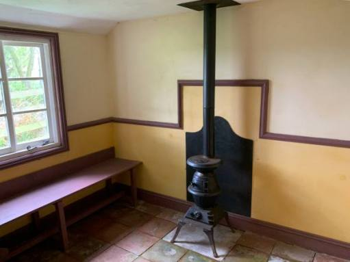 Pot-bellied stove inside the tiled and simply painted Goose House.