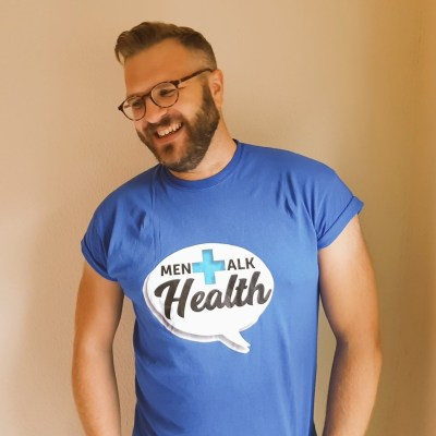 A white man with a short beard and glasses wearing a blue t-shirt that says 'Men Talk Health'. He is smiling and looking to the left of the frame.