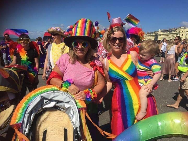 dawn rosie and ella ray at pride wearing colourful rainbow decorations and lots of people in the background