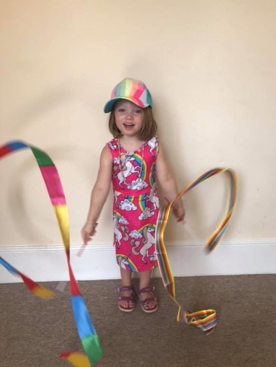 ella ray with a rainbow hat and rainbow streamers