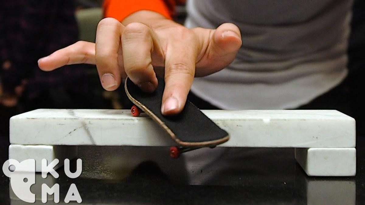 Professionelle Fingerboarder performen Tricks auf einem sich drehenden Tisch
