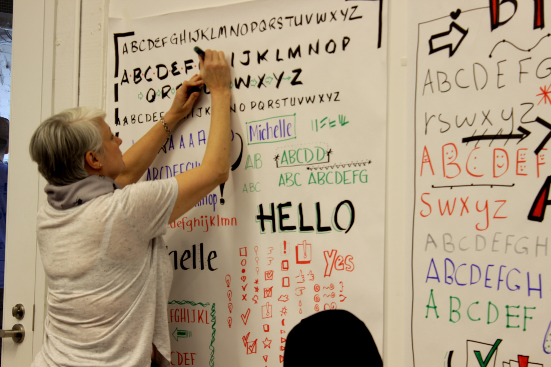 Graphic recording workshop participant working on their lettering styles