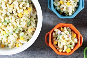 Macaroni & Cheese Salad combines elbow macaroni, cheese cubes, celery, red onion, Dijon mustard, mayo, sour cream, salt, pepper, and sugar.