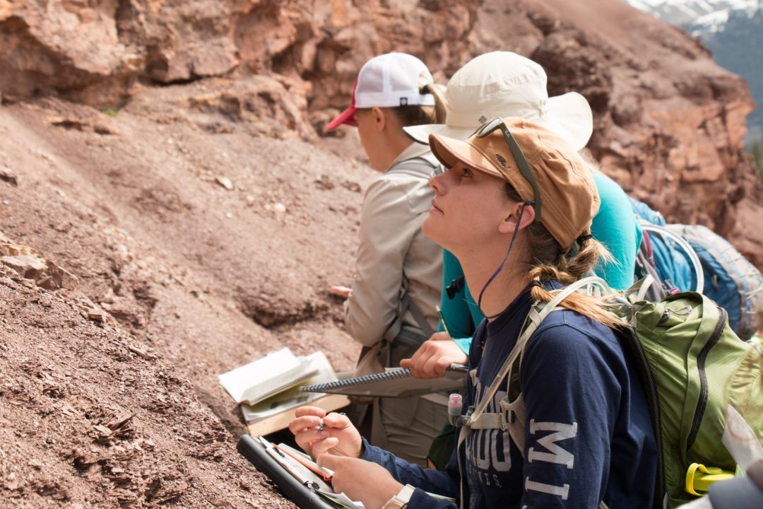 Woman examining a rock formation, taking notes on a clipboard