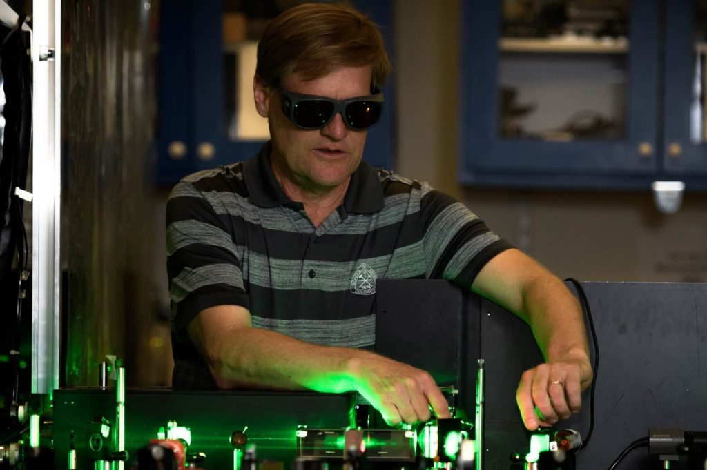 Student working in a darkened lab with protective goggles on