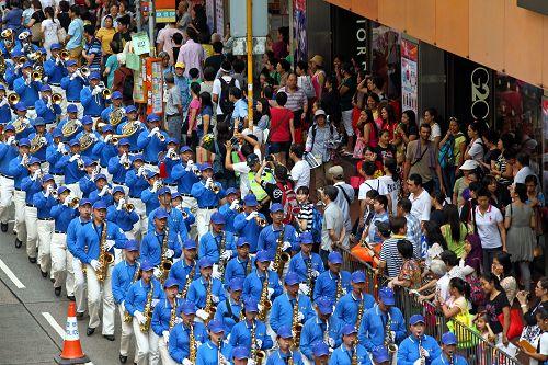 图7-11:香港法轮功学员二零一四年十月一日举行游行,队伍途经多个闹市区,吸引不少市民驻足观看。