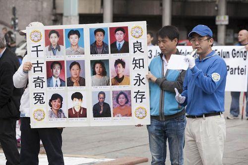 图2:郭居峰(右)在德国科隆讲述中共迫害法轮功真相,展板中他认识的十二名法轮功学员全部在迫害中失去了生命。