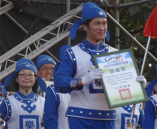 '图4:万丹乡长致赠感谢状给天国乐团指挥。'
