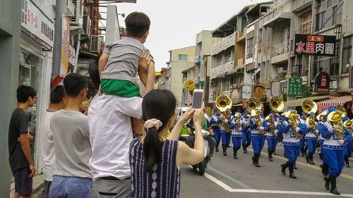'图3:很多市民拿手机争相对着行进中的天国乐团拍照。'