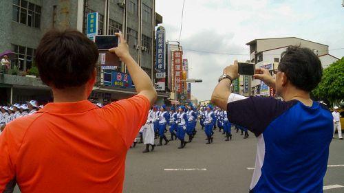 '图4:很多市民拿手机争相对着行进中的天国乐团拍照。'