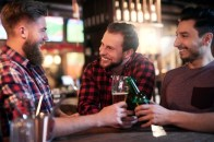 three-smiling-men-drinking-beer-pub_329181-18340