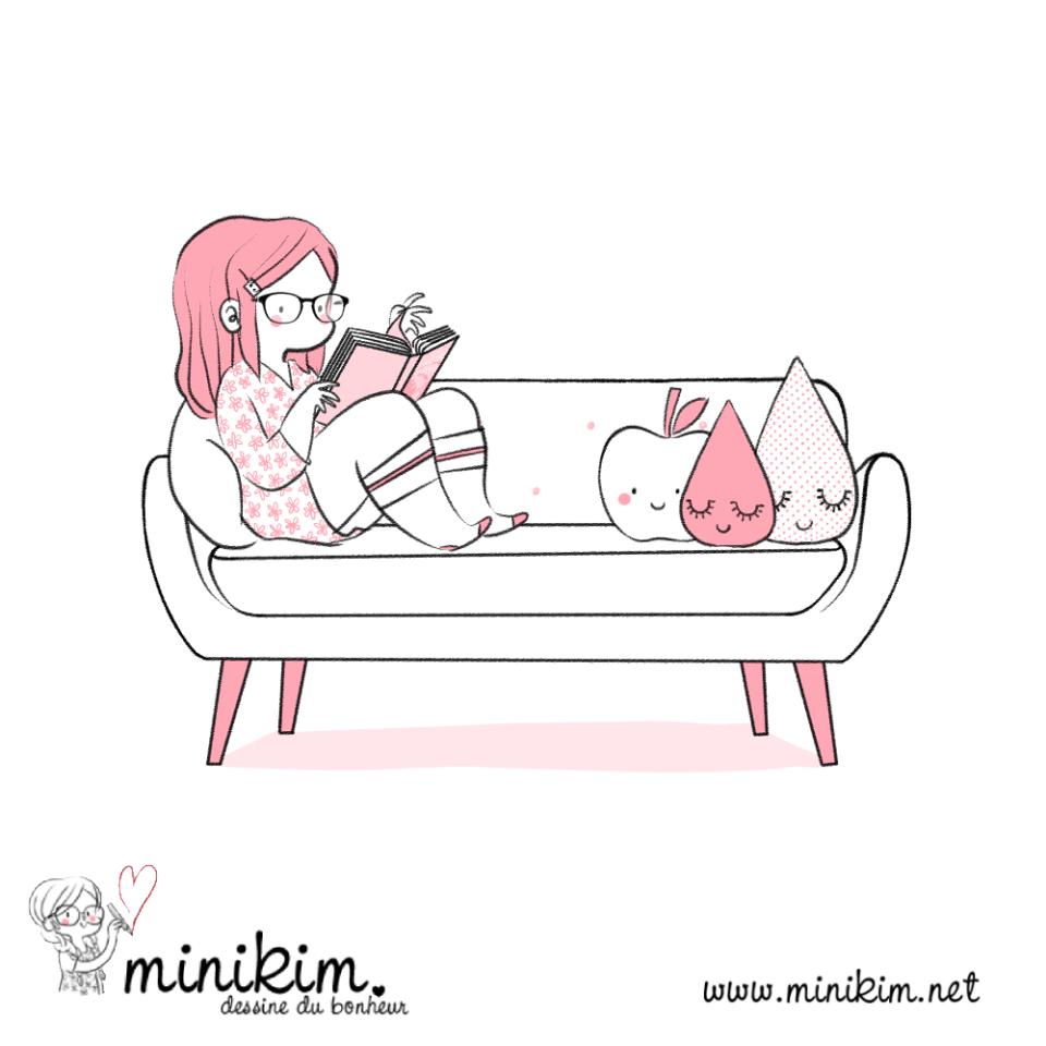 Illustration de Minikim qui représente une femme assise sur un divan en train de lire un livre. Il y a des coussins mignons sur le divan.