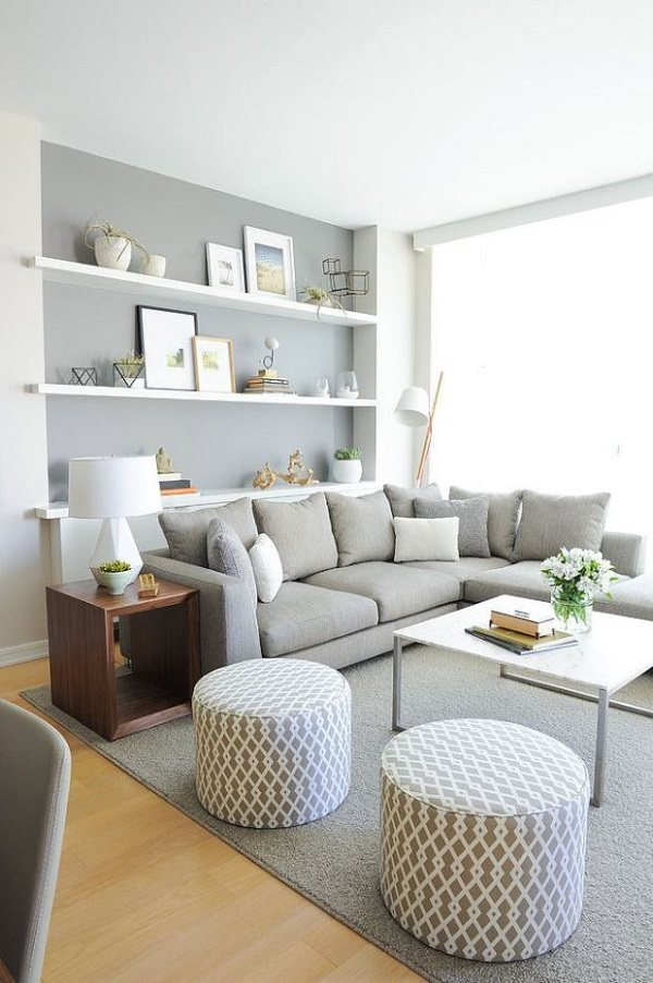 Grises paredes de la sala de estar sofá gris estantes flotantes blancas alfombra gris