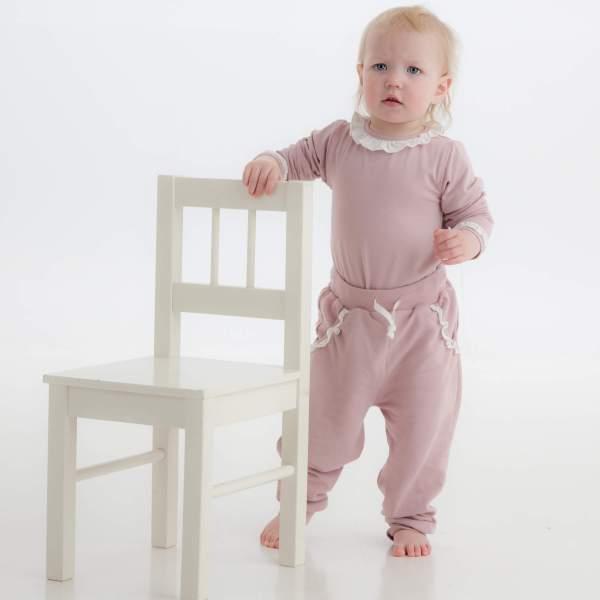 Støvet rosa bukse på modell stående