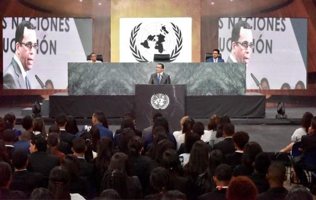 imagen Ministro Andrés Navarro desde podium de pie hablando a mas de 700 estudiantes del programa del Modelo de las Naciones Unidas del Ministerio de Educación