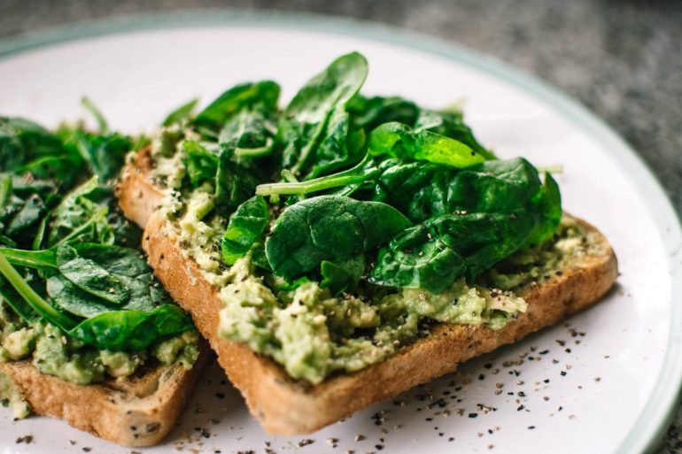 basil leaves and avocado on sliced bread on white ceramic plate