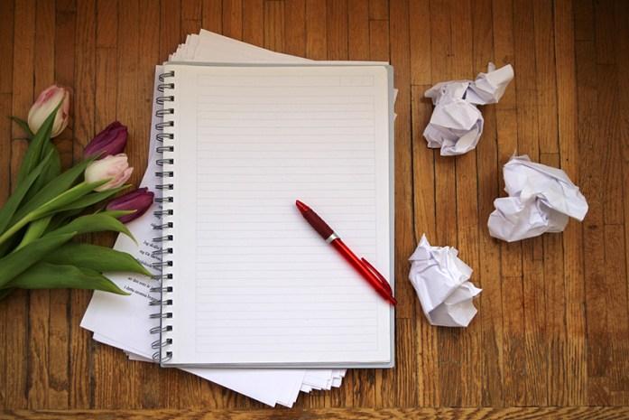 Skrivkramp. Ett tomt kollegieblock med en röd kulspetspenna på. Hopknycklade papper på höger sida, några tulpaner i rosa och lila till vänster. Allt på en nött träskiva.