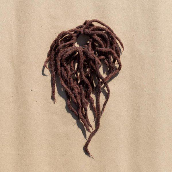 Rastarenksu-hiuslenkki, ruskeita villasuikaleita kiinnitettynä elastiseen hiuslenkkiin