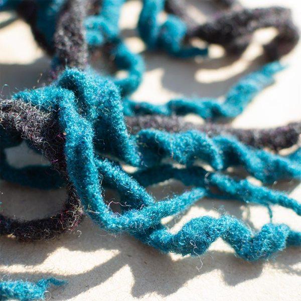 Rastarenksu-hiuslenkki, turkooseja ja harmaita villasuikaleita kiinnitettynä elastiseen hiuslenkkiin