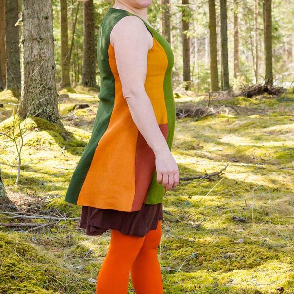 Vihreä-oranssi pellavatunika, jossa isot taskut. Sivulta päin kuvattu.