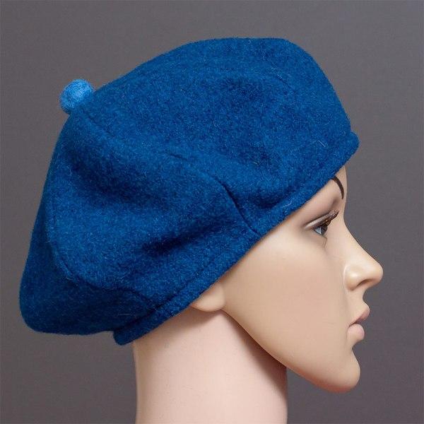 Villainen sininen baskeri, jossa hauska pompula koristeena päälaella