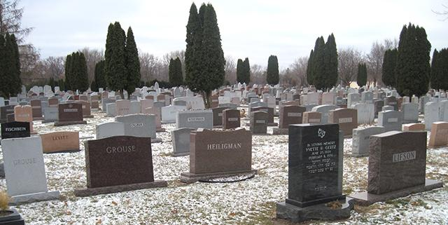 The headstones are in tight rows, packed in together without regard for height a