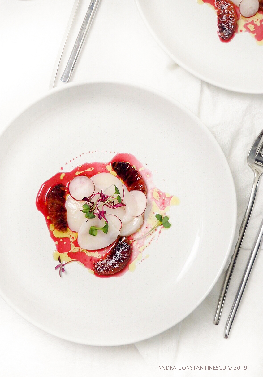 A fine dining dinner setting featuring a starter of wild scallop carpaccio garnished with blood orange and olive oil vinaigrette
