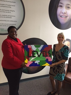 The Junior Achievement painting was done by Jaiona Head this summer. Margaret Trimer-Hartley accepts it from Mint board member Erika Davis.
