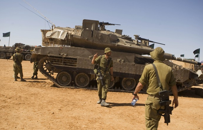 "In this Oct. 12, 2010 file photo, Israeli soldiers walk next to the tank Merkava ""Mark 4"" as they take part in a large military exercise at the Shizafon Armored Corps Training Base in the Arava desert, north of the city of Eilat, southern Israel. (AP Photos/Dan Balilty, File)"