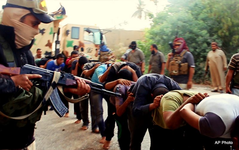 This undated file image posted on a militant website on Saturday, June 14, 2014, which has been verified and is consistent with other AP reporting, appears to show militants from the al-Qaida-inspired Islamic State of Iraq and the Levant, who now call themselves the Islamic State, leading away captured Iraqi soldiers dressed in plain clothes after taking over a base in Tikrit, Iraq