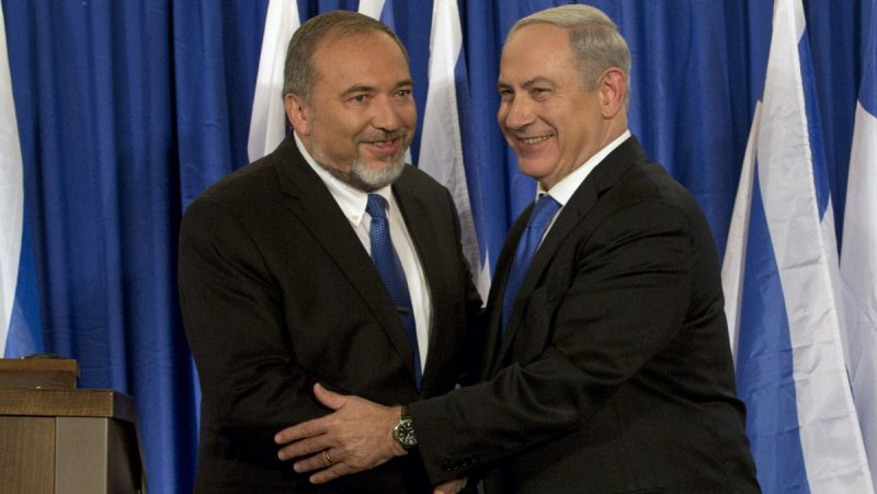 Israeli Prime Minister Benjamin Netanyahu, right, and Foreign Minister Avigdor Lieberman shake hands in front the media after giving a statement in Jerusalem. (AP Photo/Bernat Armangue)