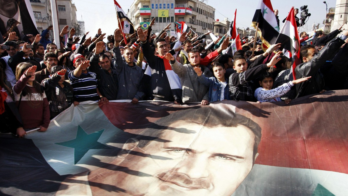 FILE - In this Monday, Dec. 19, 2011 file photo, Syrians hold a large poster depicting Syria's President Bashar Assad during a rally in Damascus, Syria. Some activists expressed regret that one year later their
