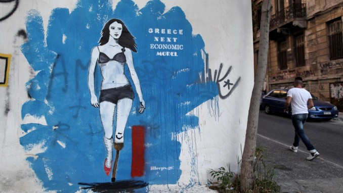 A man walks next a graffiti in central Athens on Tuesday, June 19, 2012. (AP Photo/Petros Giannakouris)