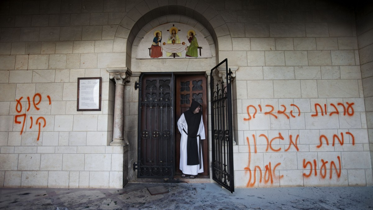 In this Sept. 4, 2012, file photo, a Catholic monk stands in a doorway of the Latrun Trappist Monastery where Israeli police say vandals spray-painted anti-Christian and pro-settler graffiti and set the monastery's door on fire, in Latrun, between Jerusalem and Tel Aviv, Israel. (AP Photo/Oded Balilty, File)