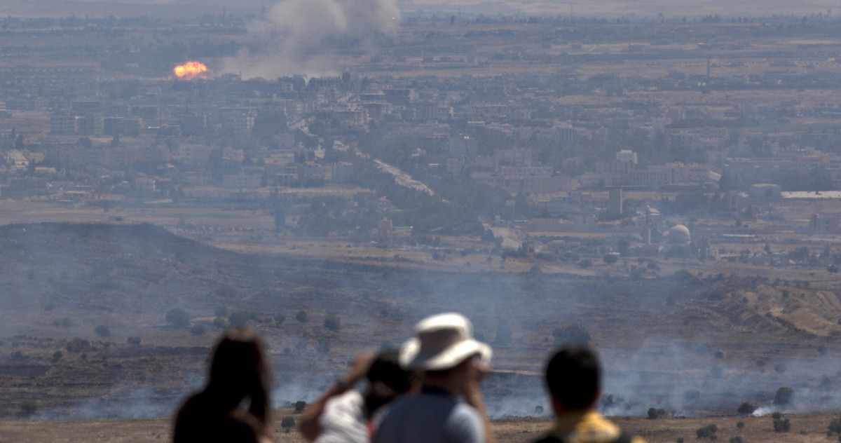 Israeli tourists look at fire caused by fighting in Syria from an observation point on Mt. Bental in the Golan Heights, near the border between Syria and Israel, Friday, June 7, 2013. (AP/Sebastian Scheiner)